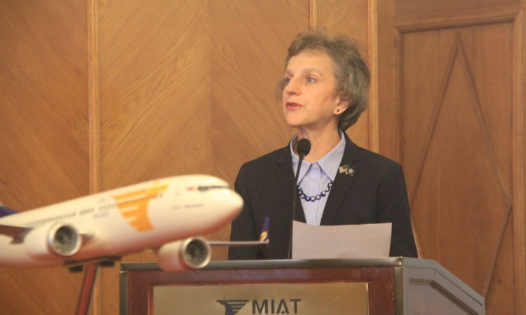 A woman standing behind a podium and an airplane figure